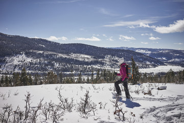 Side view of female hiker with backpack walking on snow covered mountain against sky during sunny day