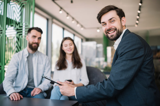 Portrait of real estate agent help to choosing house for young couple, meeting in modern office. Good service for clients. Life insurance concept.