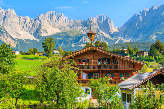 Typical wooden alpine house against Alps mountains background on green meadow in Going am Wilden Kaiser village on sunny summer day, Tyrol, Austria