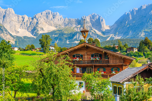 Wall mural Typical wooden alpine house against Alps mountains background on green meadow in Going am Wilden Kaiser village on sunny summer day, Tyrol, Austria