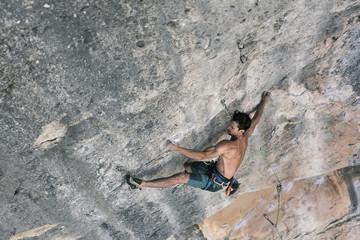 High angle view of shirtless man rock climbing