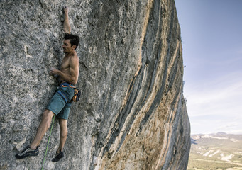 Side view of shirtless man rock climbing against sky