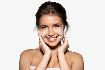 Fototapeta Portrait of joyful young woman applying white foam for washing. Cheerful brunette with perfect clean skin looking at camera with gladness. Skincare spa relax concept. Isolated on grey background