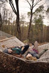 Full length of friends lying on hammock against trees
