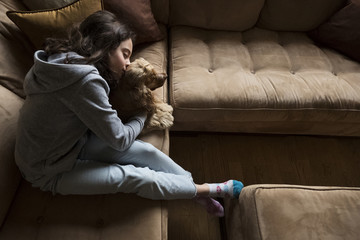 High angle view of girl kissing Cocker Spaniel while relaxing on sofa at home