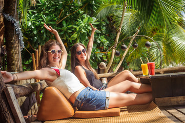 Two girlfriends drinking fruit cocktail on a tropical beach