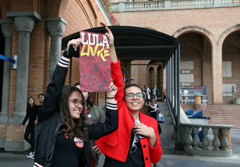 """Supporters of Presidential candidate Fernando Haddad of the Workers Party (PT) hold a sign reading """"free Lula"""" during a campaign rally at the Basilica of the National Shrine of Our Lady of Aparecida"""