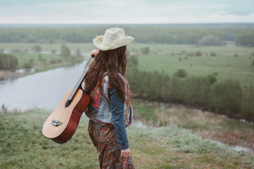 Trends dress style 2017. The concept of freedom and youth lifestyle. Girl in skirt with patterns and denim shirt in nature with guitar. Editorial use only