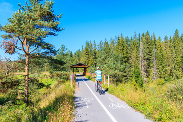 Young woman riding bike on cycling track around Tatra Mountains near Czarny Dunajec village. The end point is in Trstena village in Slovakia.