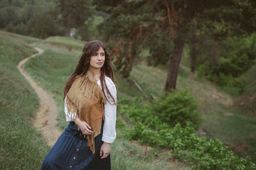 Hippie girl in white dress and velvet jacket in nature. Freedom and lifestyle. Retro clothing and accessories. The landscape of fields and river. Close-up portrait.