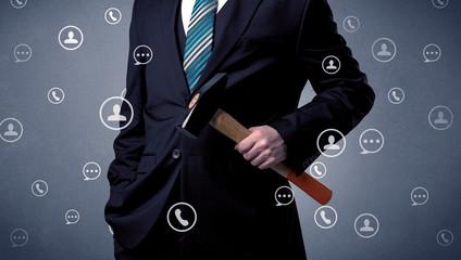 Thoughtful businesman holding tool with communication symbols around