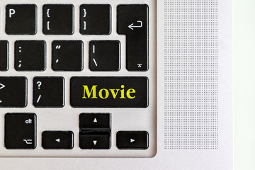 "top view isolated laptop keyboard with yellow ""movie"" text on button, concept design f"