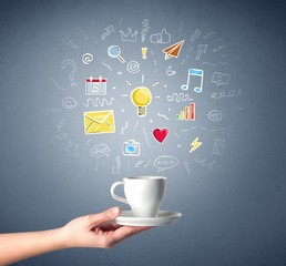 Young female hand holding coffee cup with colorful communication related drawings above it