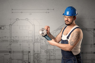 Worker standing with tool in his hand in front of technical drawings.
