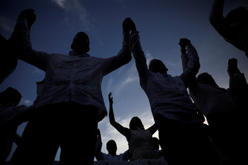 People pray during a commemorative event organized by the local government a year after Hurricane Maria devastated Puerto Rico, in San Juan, Puerto Rico