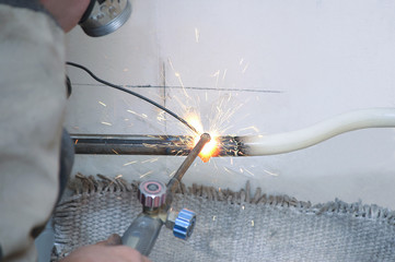 Welding of pipes. Plumber on home repair.