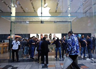 Apple Store staff greets customers who have been waiting in line to purchase Apple's new iPhone XS and XS Max in Tokyo