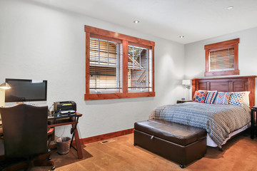 Bedroom interior with leather bench and wooden desk.