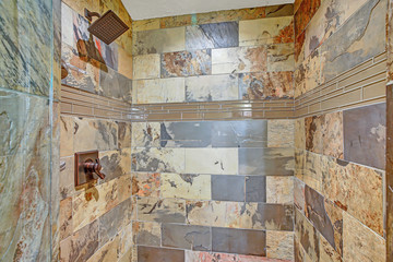 Large walk-in shower with natural stone tiled interior
