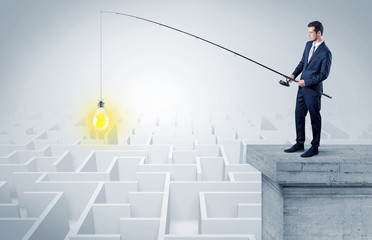 Young businessman fishing new idea concept on the top of a building from a maze