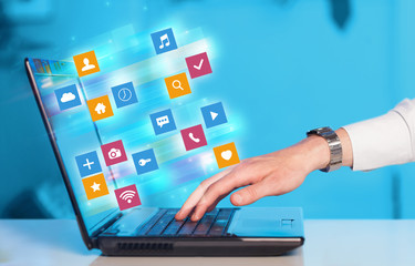 Hand using laptop with colorful fast moving application icons and symbols concept