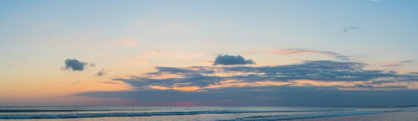 Panorama, Banner, long format of Sunset on the Kuta beach with reflection in the water on the island of Bali