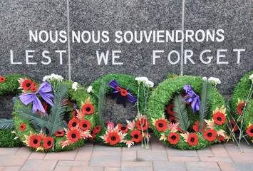 Wreaths laid in front of Lest We Forget sign in Remembrance Day celebration