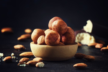 Marzipan, round almond candies in wooden bowl on dark table, selective focus