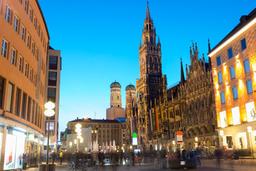 People walking at Marienplatz square and Munich city hall in night in Munich, Germany. Cafes, bars, shops and restaurants. Motion blurred people.