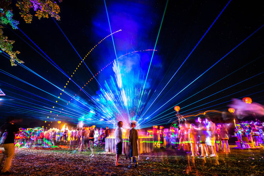 Outdoor night music party with laser lights and fire