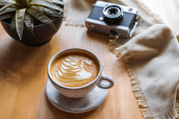 Сups of cappuccino with a beautiful pattern on milk foam. Wooden table with place for text, flower and camera, retro . The view from the top