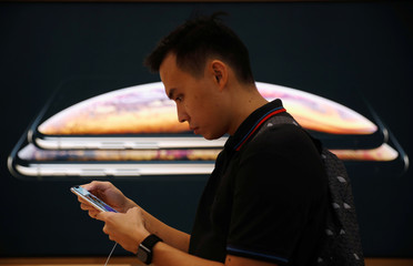 A customer uses an iPhone at next to a poster of the new iPhone XS and iPhone XS Max at the Apple Store in Singapore