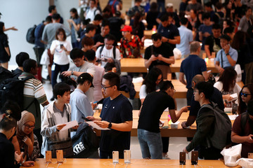 Customers look at the newly launched iPhone XS and iPhone XS Max at the Apple Store in Singapore