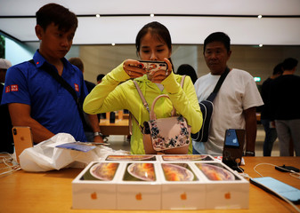 Customers from Vietnam take photos of their iPhone XS purchases at the Apple Store in Singapore
