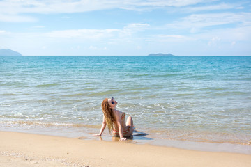 beautiful girl in bikini posing on a deserted beach. white sand, turquoise sea and a young girl.