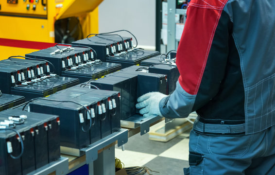 A gloved worker connects the batteries to the factory