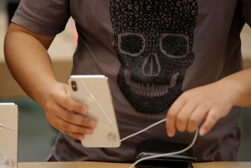 A customer places an Apple's new iPhone XS after it went on sale at the Apple Store in Beijing