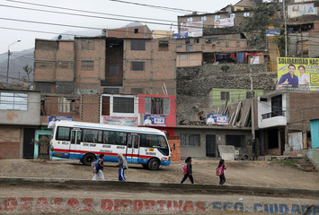People walk along a street in the Carabayllo district of Lima