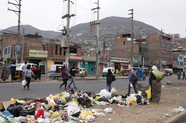 People cross a street lined with garbage at the Carabayllo district of Lima