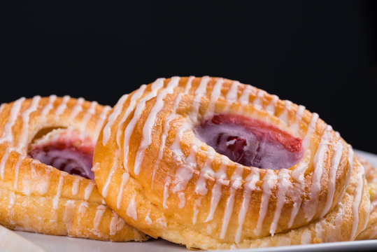 Strawberry Danish pastry against a dark background with copy space