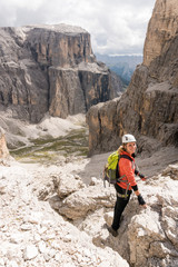 young female mountain climber descending a steep Via Ferrata in the Dolomites of Alta Badia in northern Italy with great landscape behind