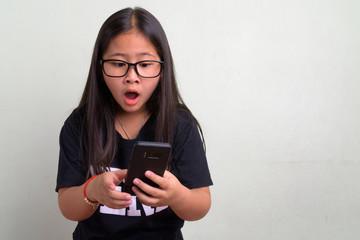 Young cute Asian nerd girl wearing eyeglasses