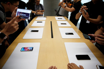 People handle the new Apple iPhone XS and iPhone XS Max during a media tour at an Apple office in Shanghai