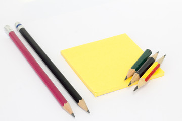 Pencil with sharpening shavings and Post-it Notes on white background