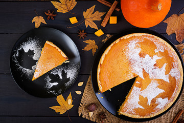 American homemade pumpkin pie with cinnamon and nutmeg, pumpkin seeds and autumn leaves on a wooden table. Thanksgiving food. Top view. Flat lay