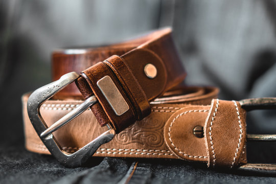Two brown leather belts on dark background