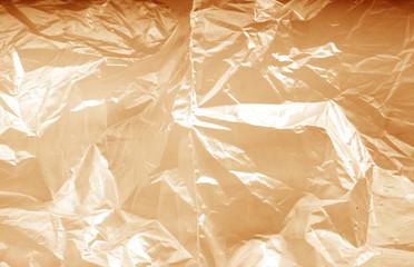Crumpled transparent plastic  surface in orange tone.