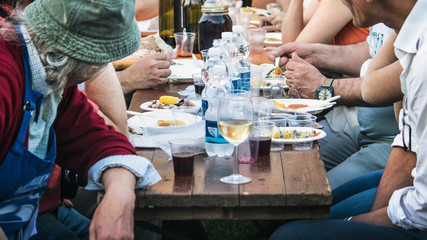 people eating in a town festival, horizontal image of a typical outdoor dinner (convivial moment of italian culture)