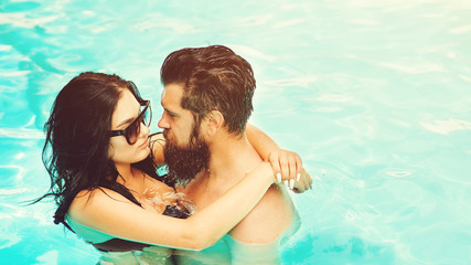 Young and attractive couple hugging in swimming pool. Dream vacation in tropical country. Swimming pool in hotel. Wet couple of sexy girl and handsome bearded man in swimming pool with blue water