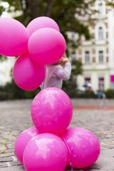 Kind mit pinkem Luftballon. Kid plays with ballon.